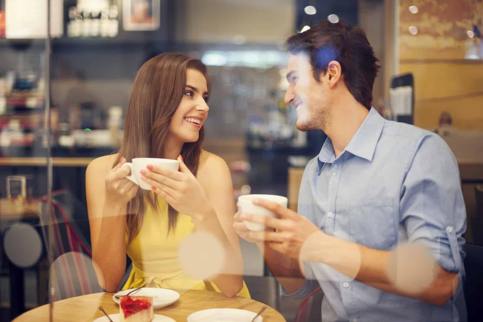 Homme et femme prenant un café assis dans un café.