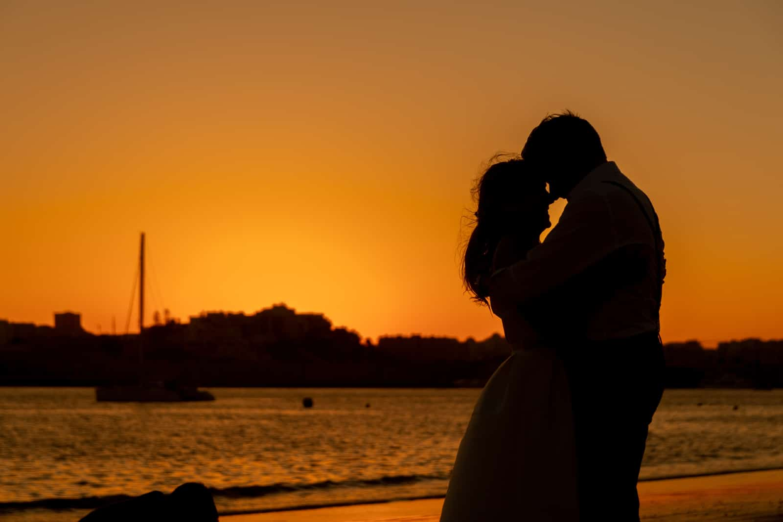 homme et femme s'embrassant en se tenant près de la mer