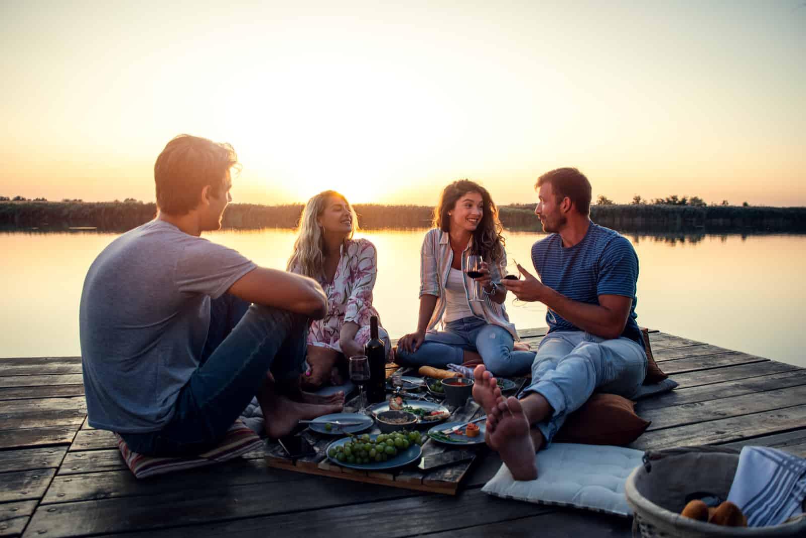 des amis s'assoient sur la jetée et parlent