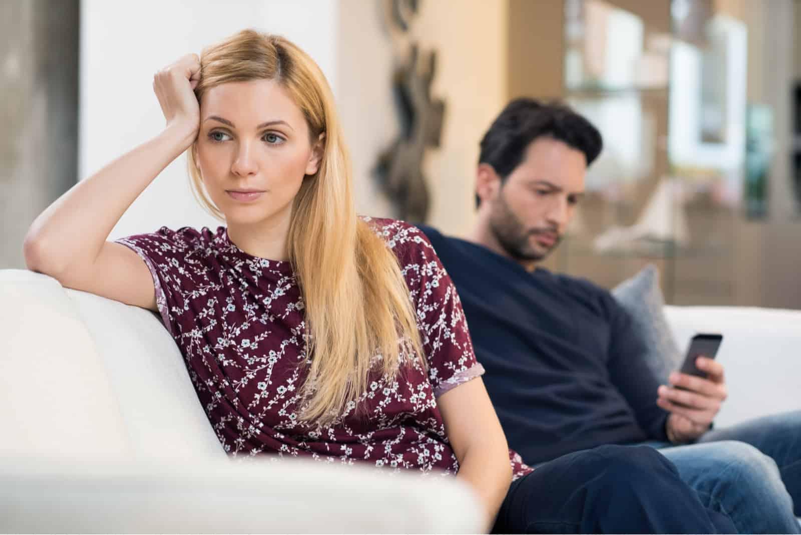 femme triste appuyée sur le canapé et assise près d'un homme