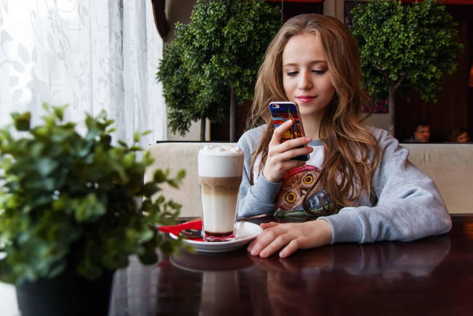 Femme regardant son smartphone assise dans un café