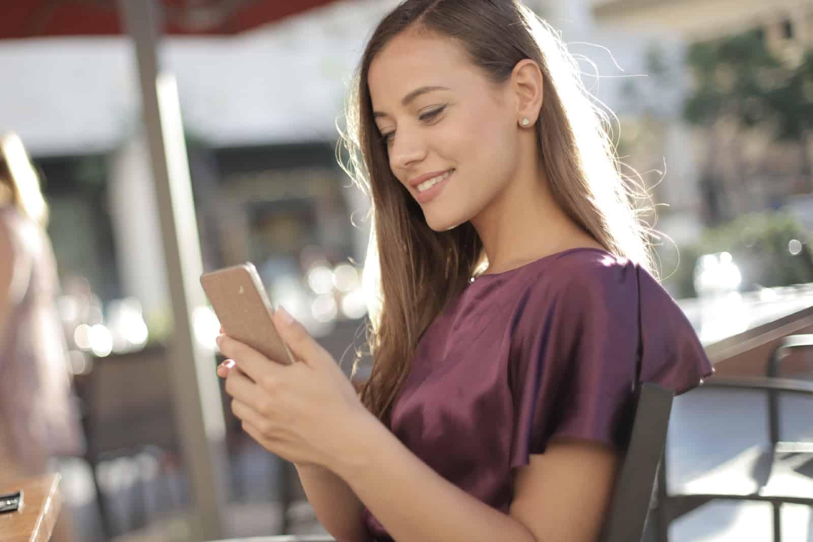 femme heureuse regardant son smartphone tout en étant assise à l'extérieur