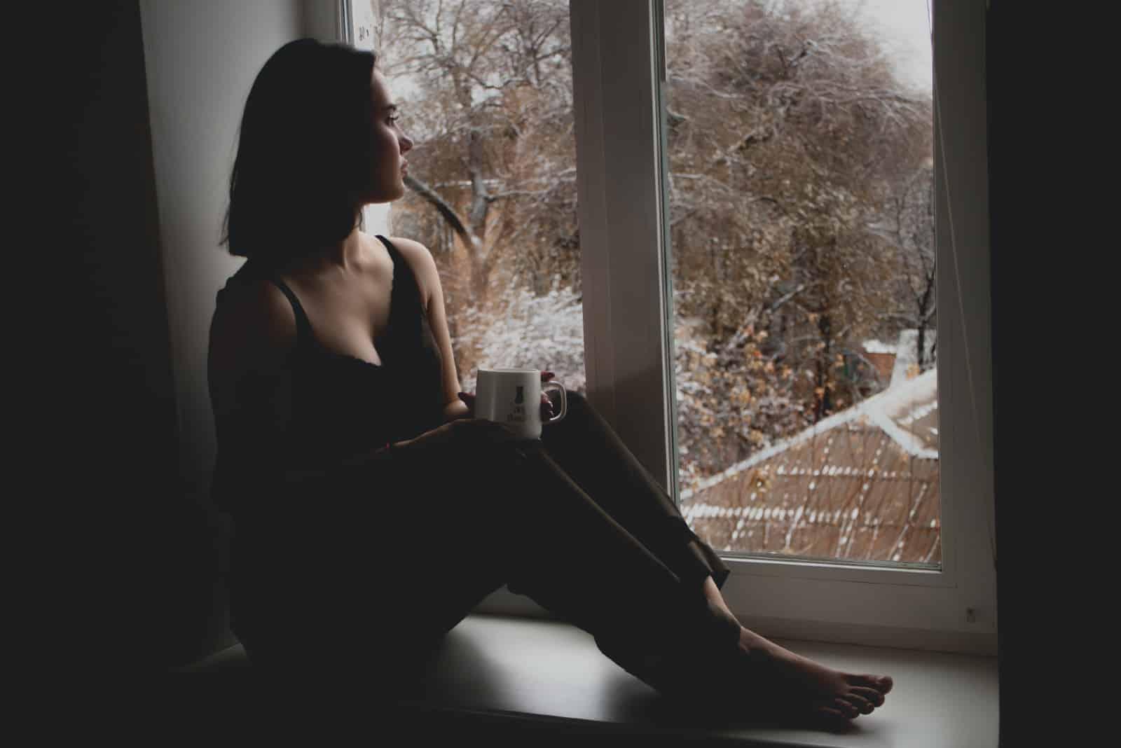 femme tenant une tasse blanche assise sur le rebord d'une fenêtre