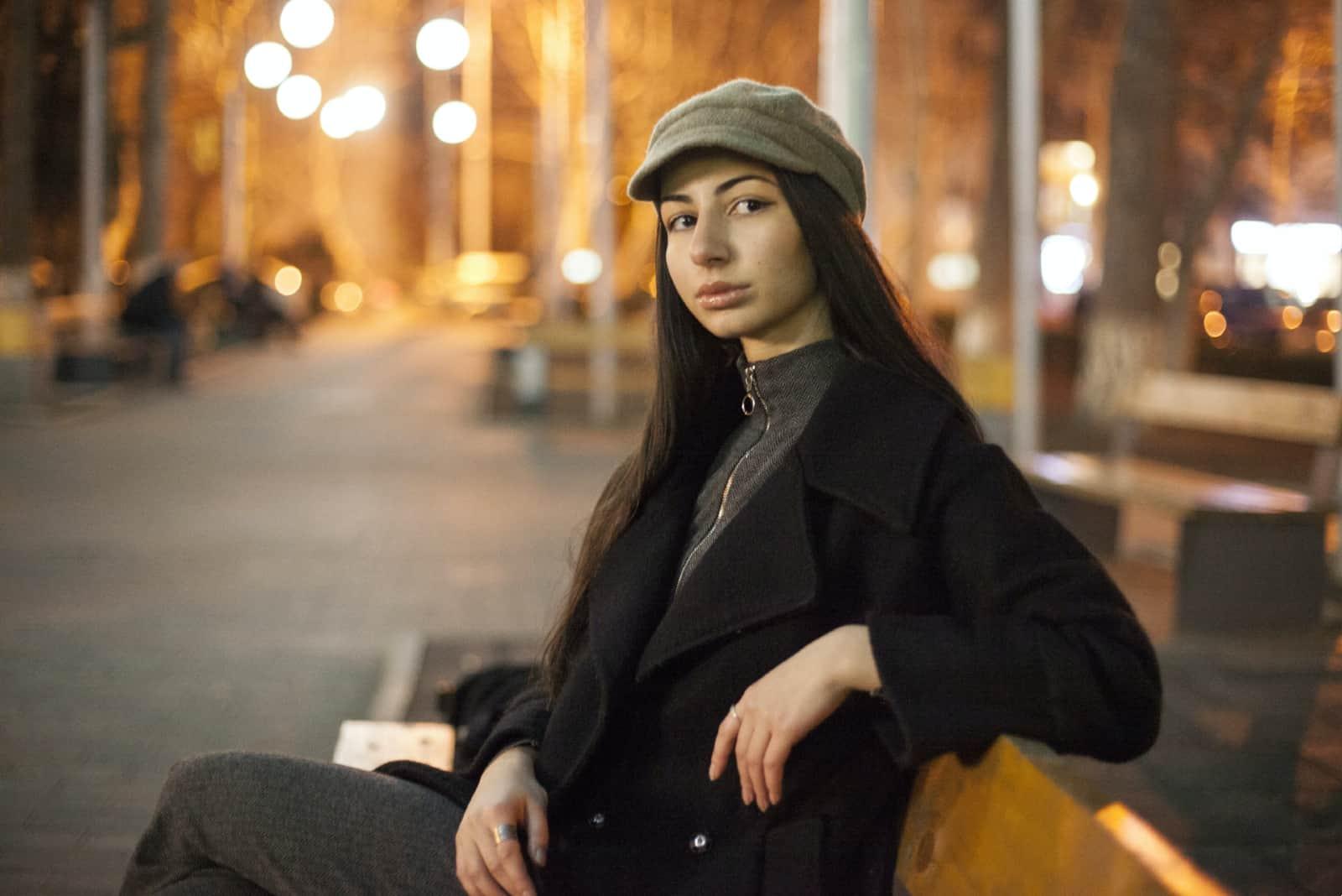femme pensive en manteau noir assise sur un banc