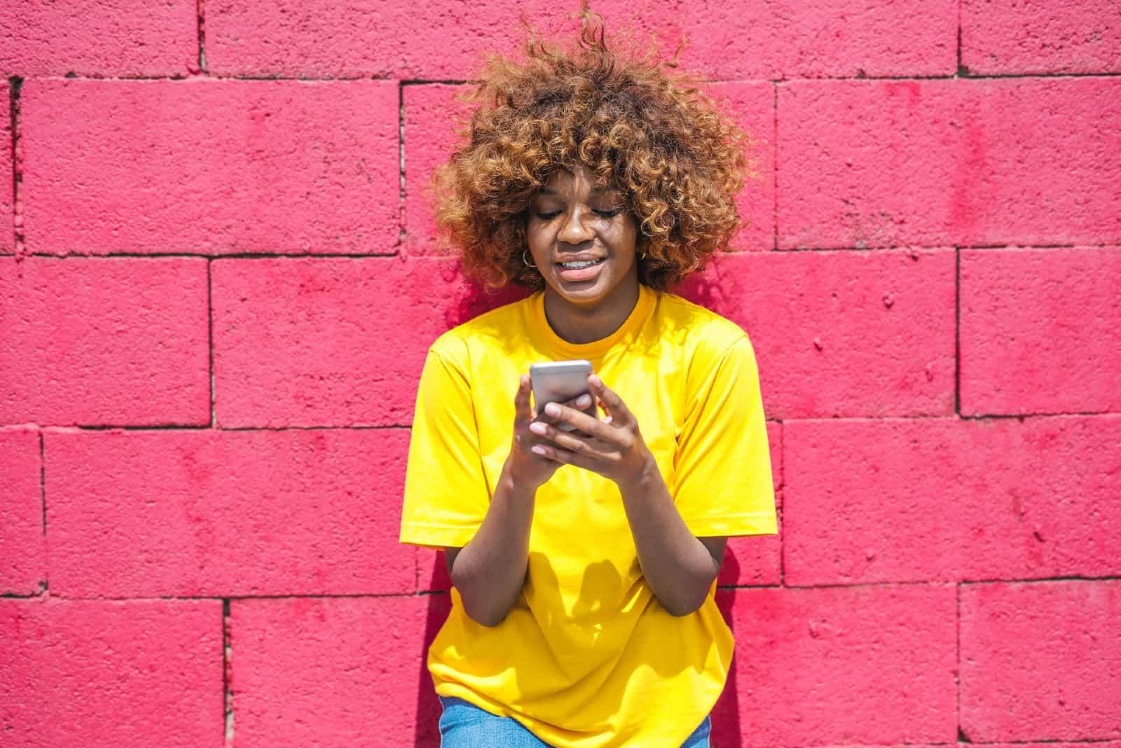 femme heureuse utilisant un smartphone tout en se tenant près d'un mur