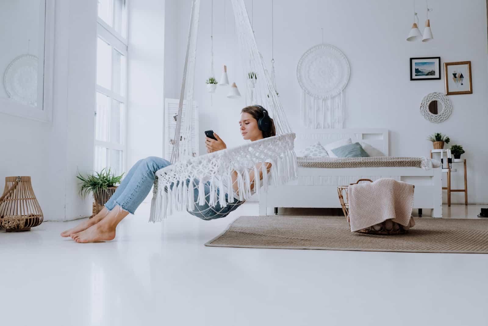 femme écoutant de la musique assise sur un hamac en intérieur