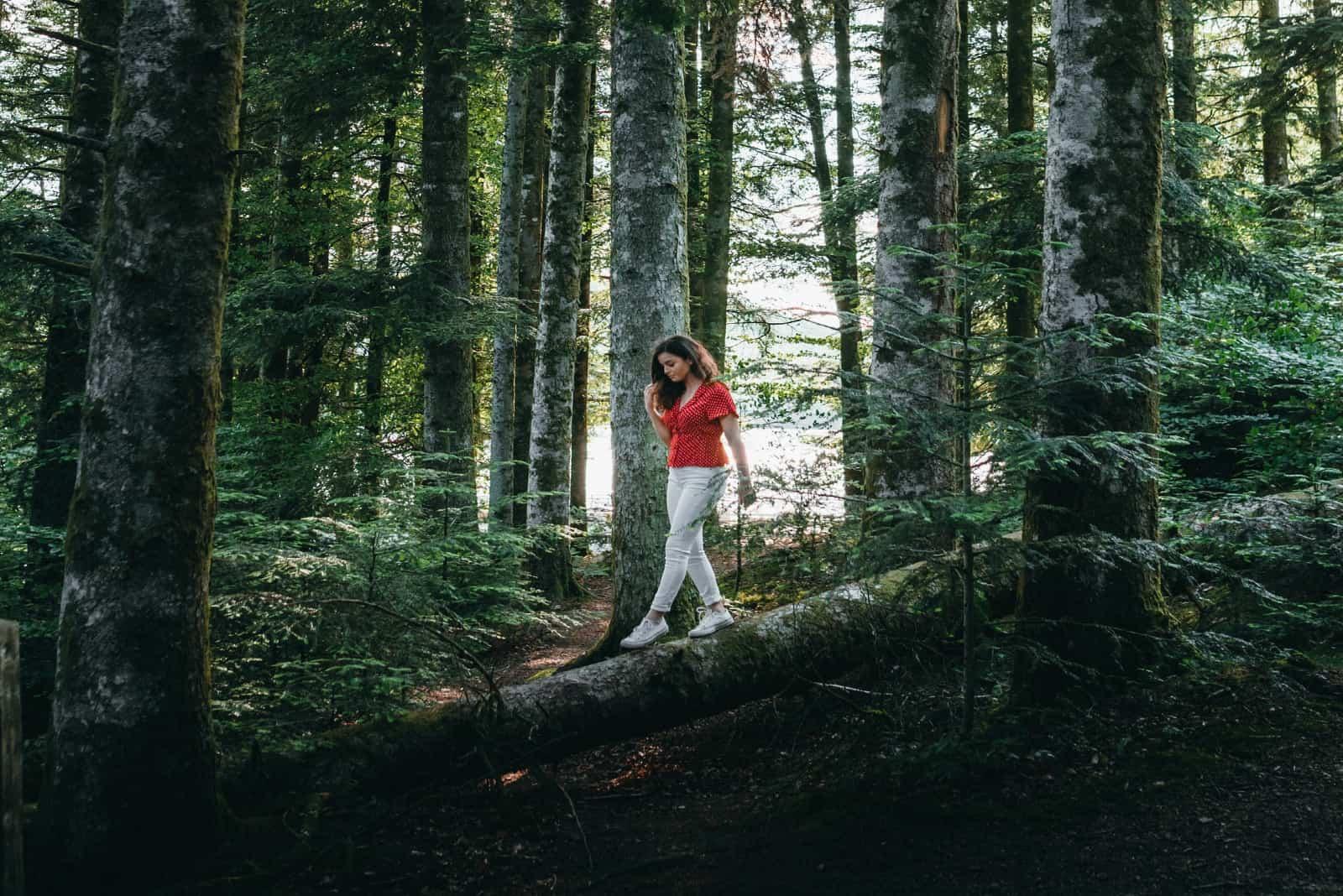 femme avec un haut rouge marchant dans les bois