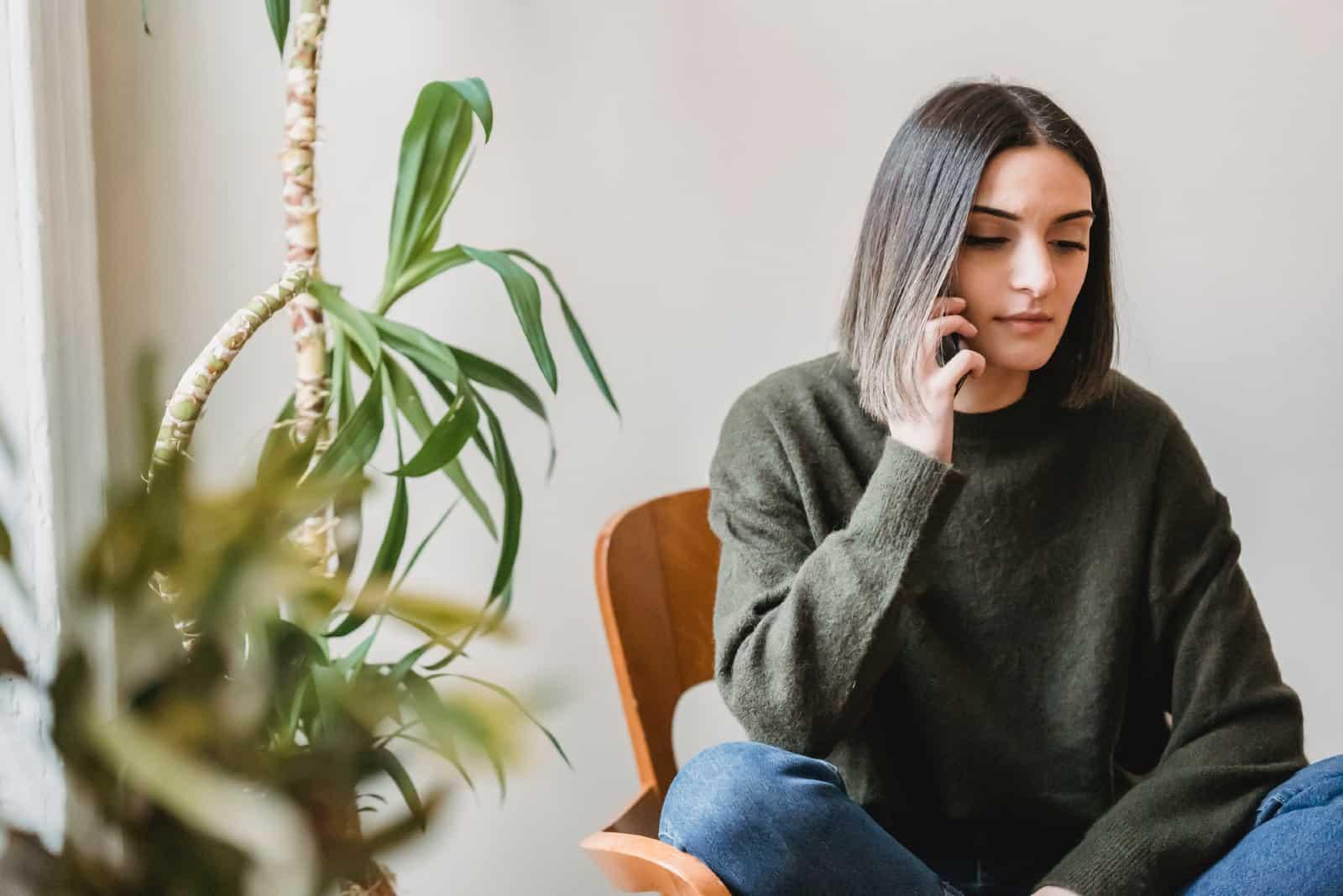 Femme parlant sur son smartphone, assise sur une chaise