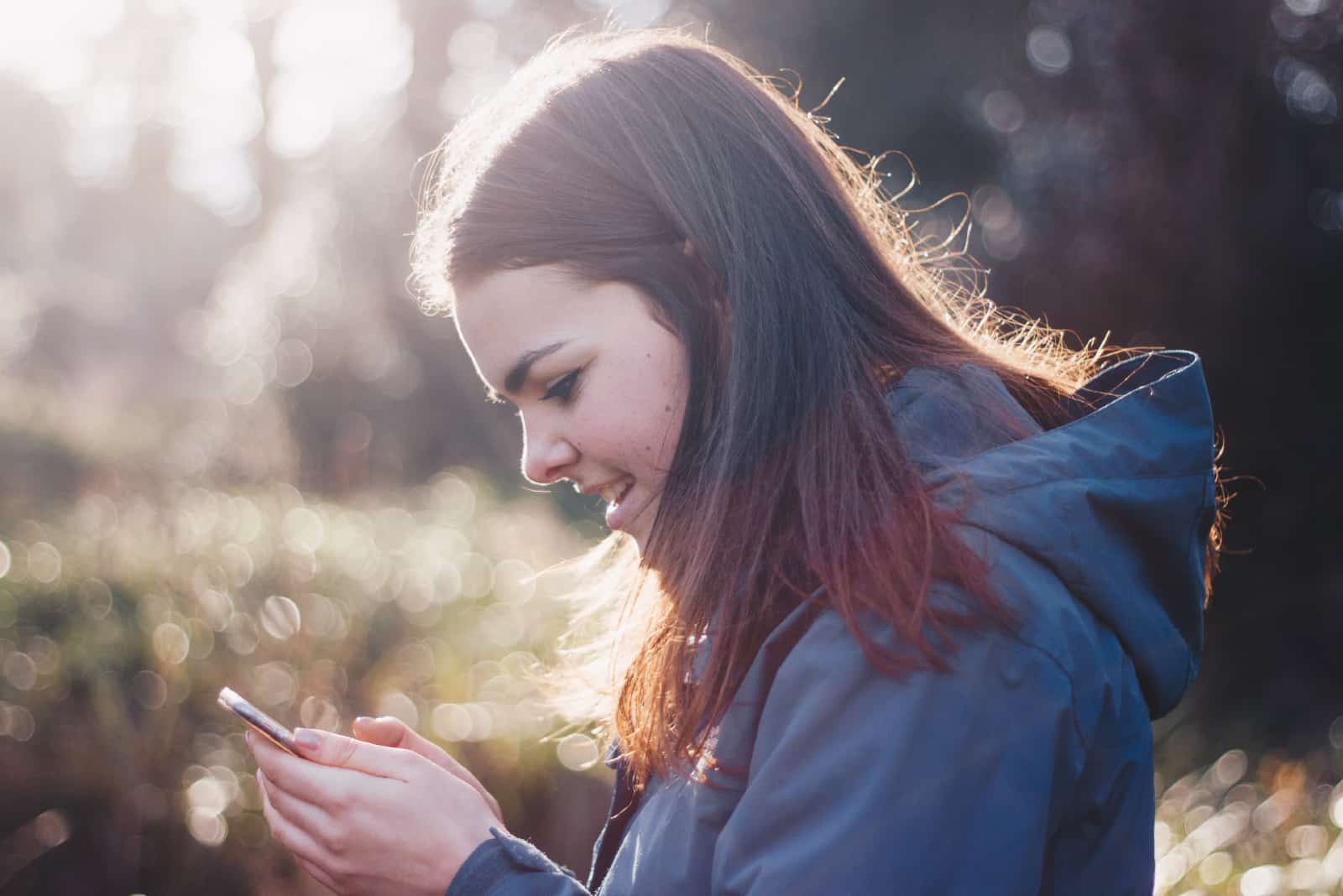 femme heureuse regardant son smartphone à l'extérieur