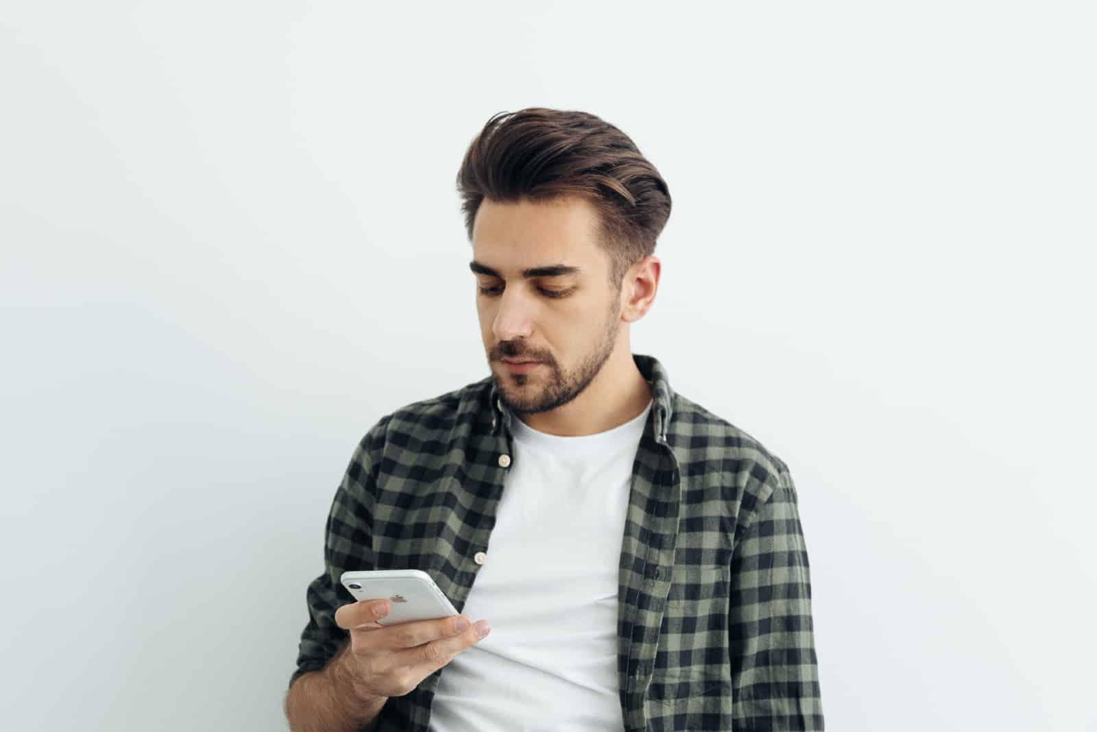 un homme regarde son smartphone en se tenant près d'un mur