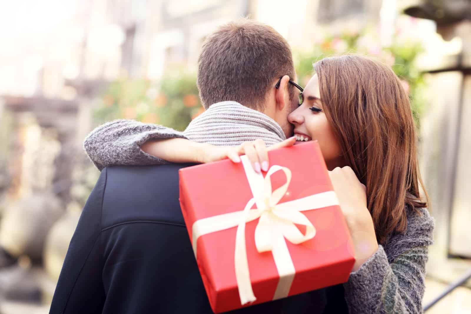 la femme a embrassé l'homme tout en tenant le cadeau dans sa main