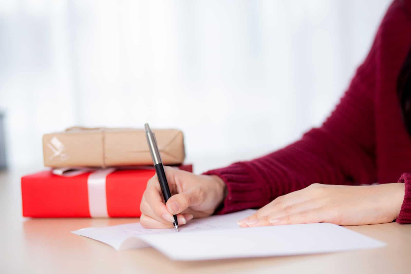la femme écrit une carte de voeux