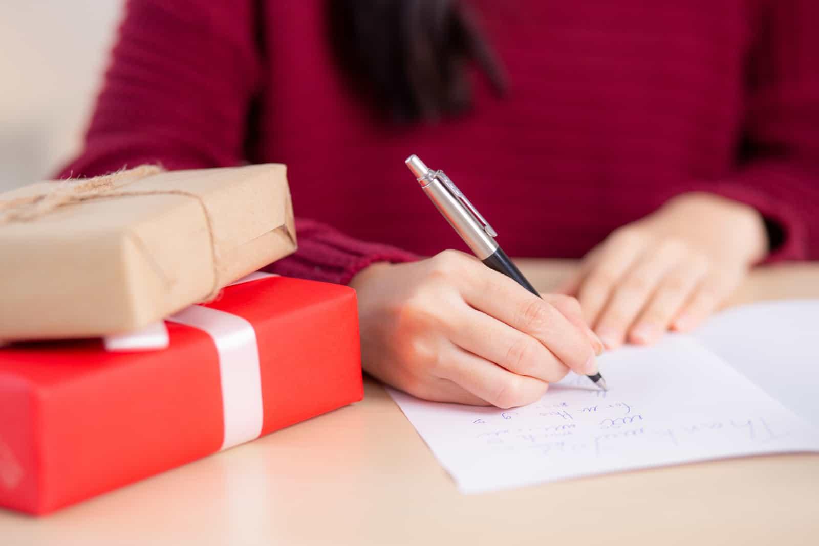 la femme est assise à table et écrit