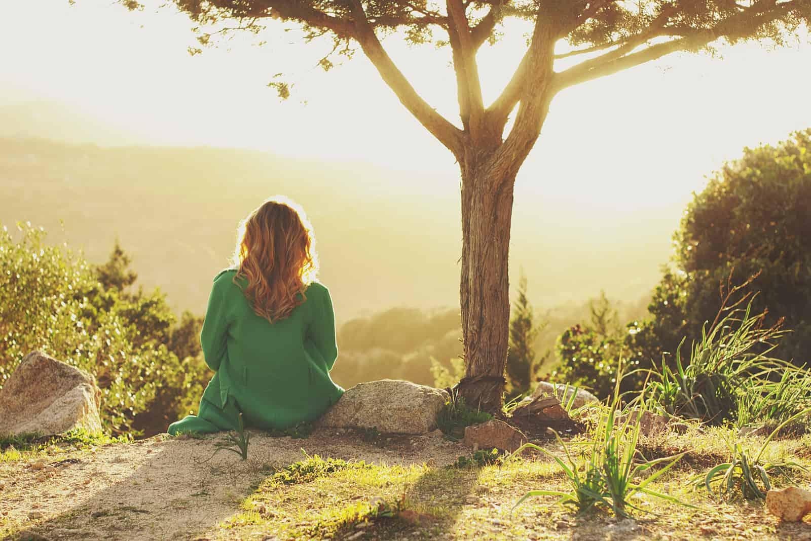 la femme est assise et regarde au loin
