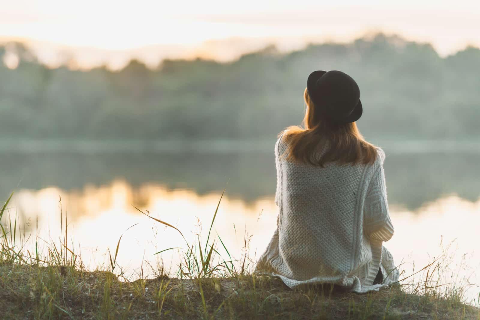 la femme est assise et regarde la rivière