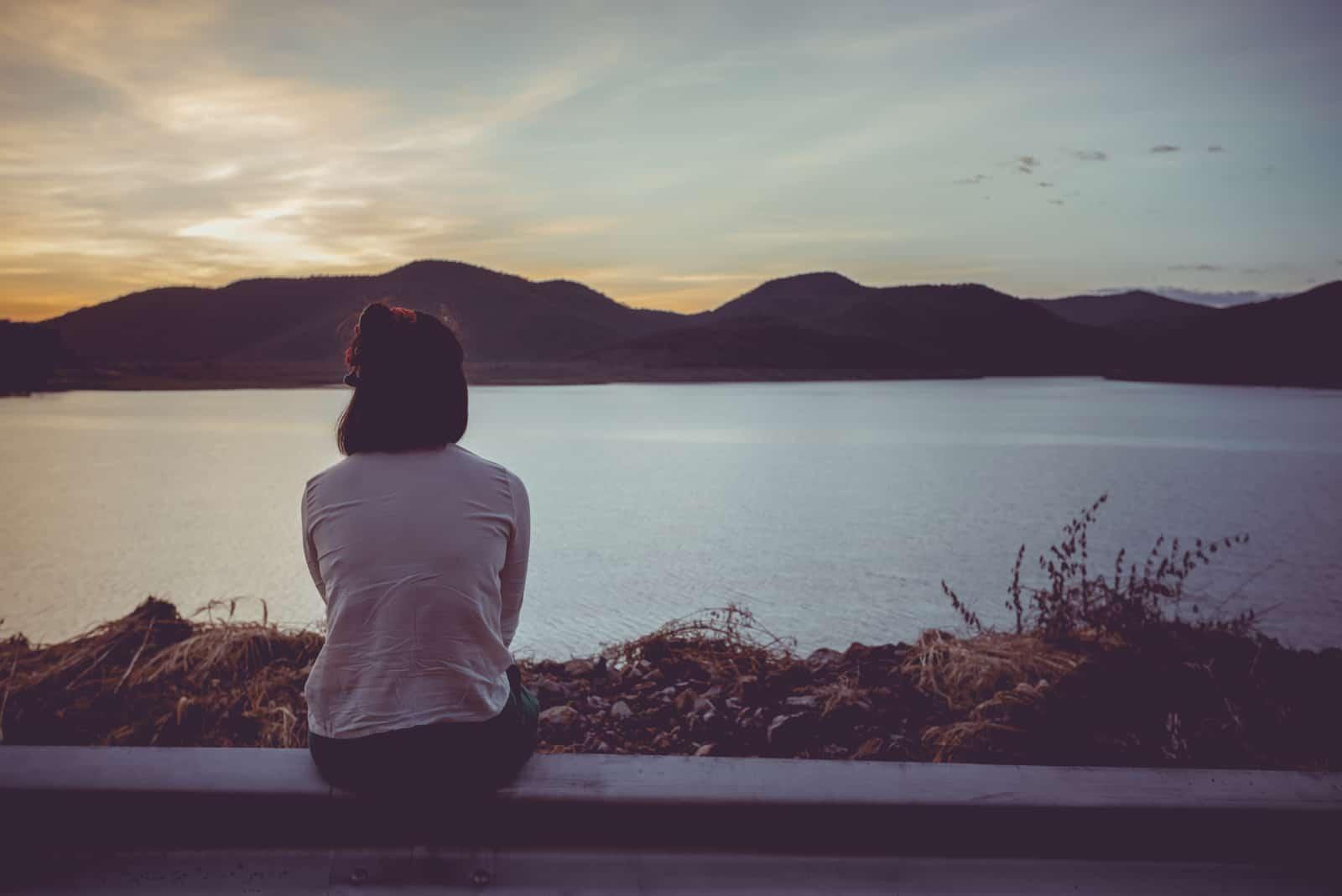 la femme est assise le dos tourné et regarde vers la mer