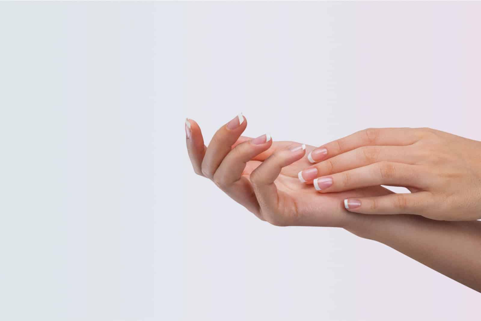 la femme se gratte la paume droite avec la main gauche