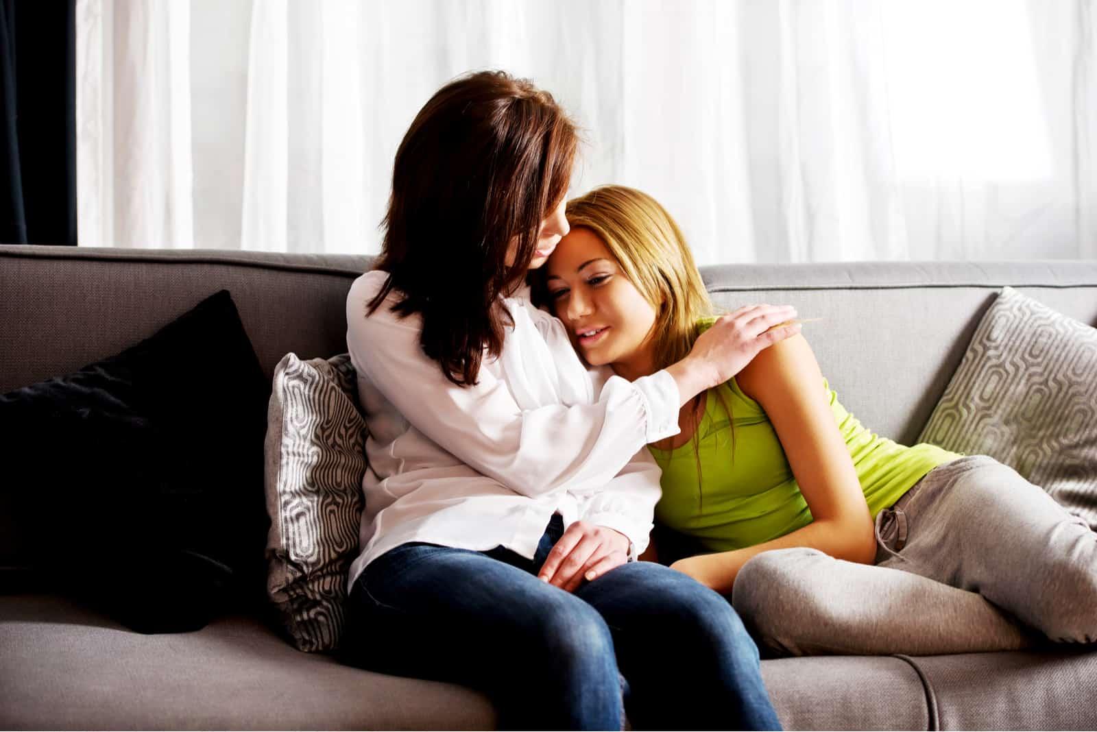 la mère a embrassé sa fille sur le canapé
