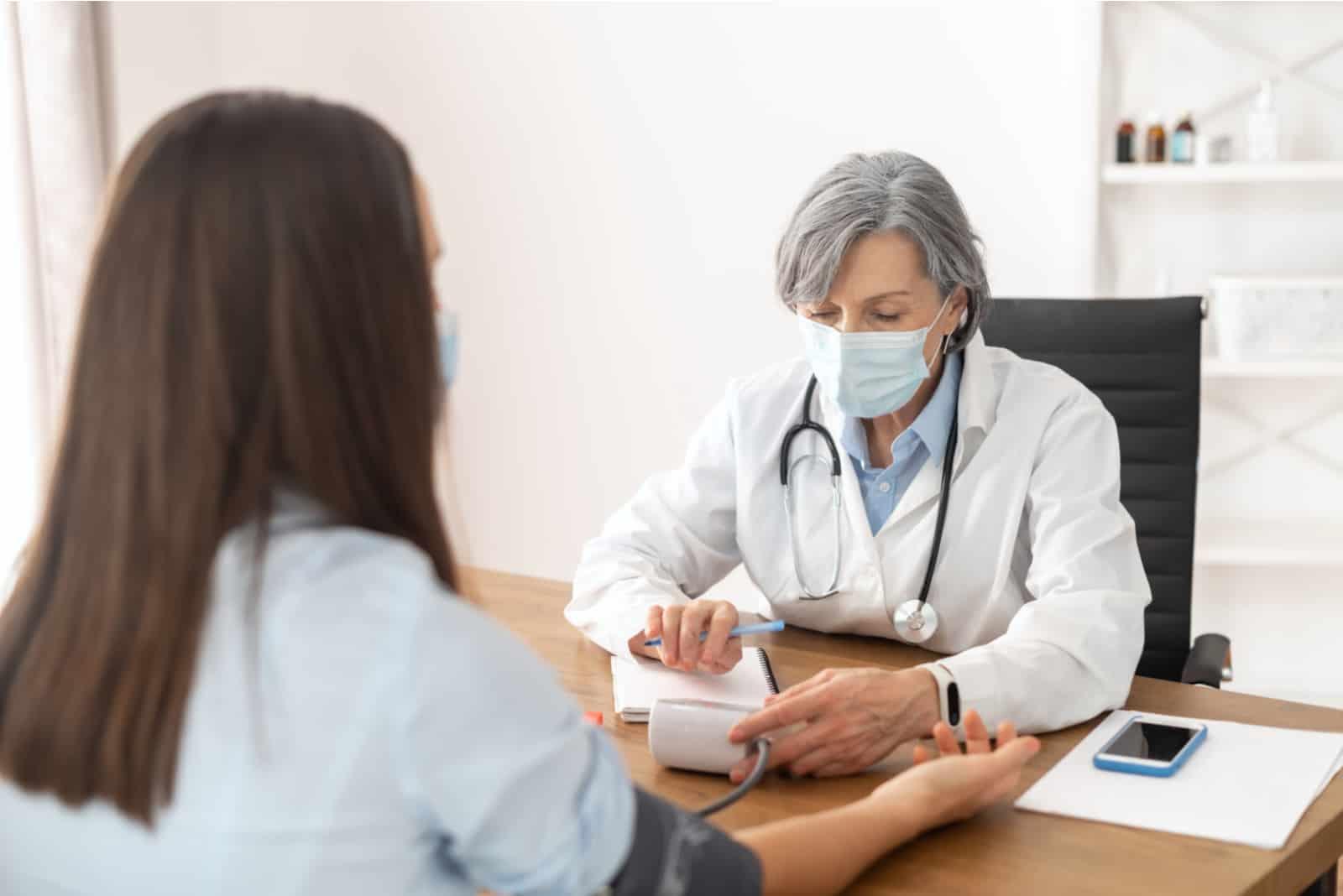 le médecin mesure la tension artérielle de la femme
