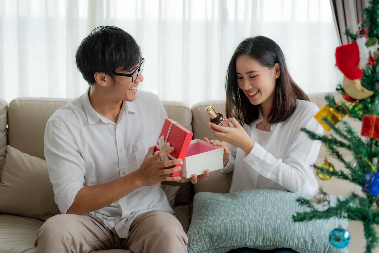 l'homme a surpris la femme avec un cadeau alors qu'ils étaient assis sur le canapé