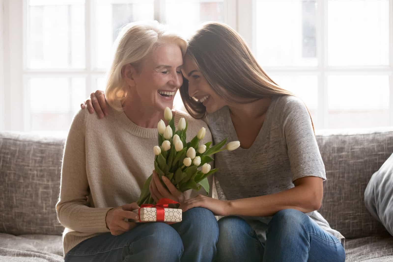 maman souriante et sa fille assise sur le canapé embrassant avec des cadeaux