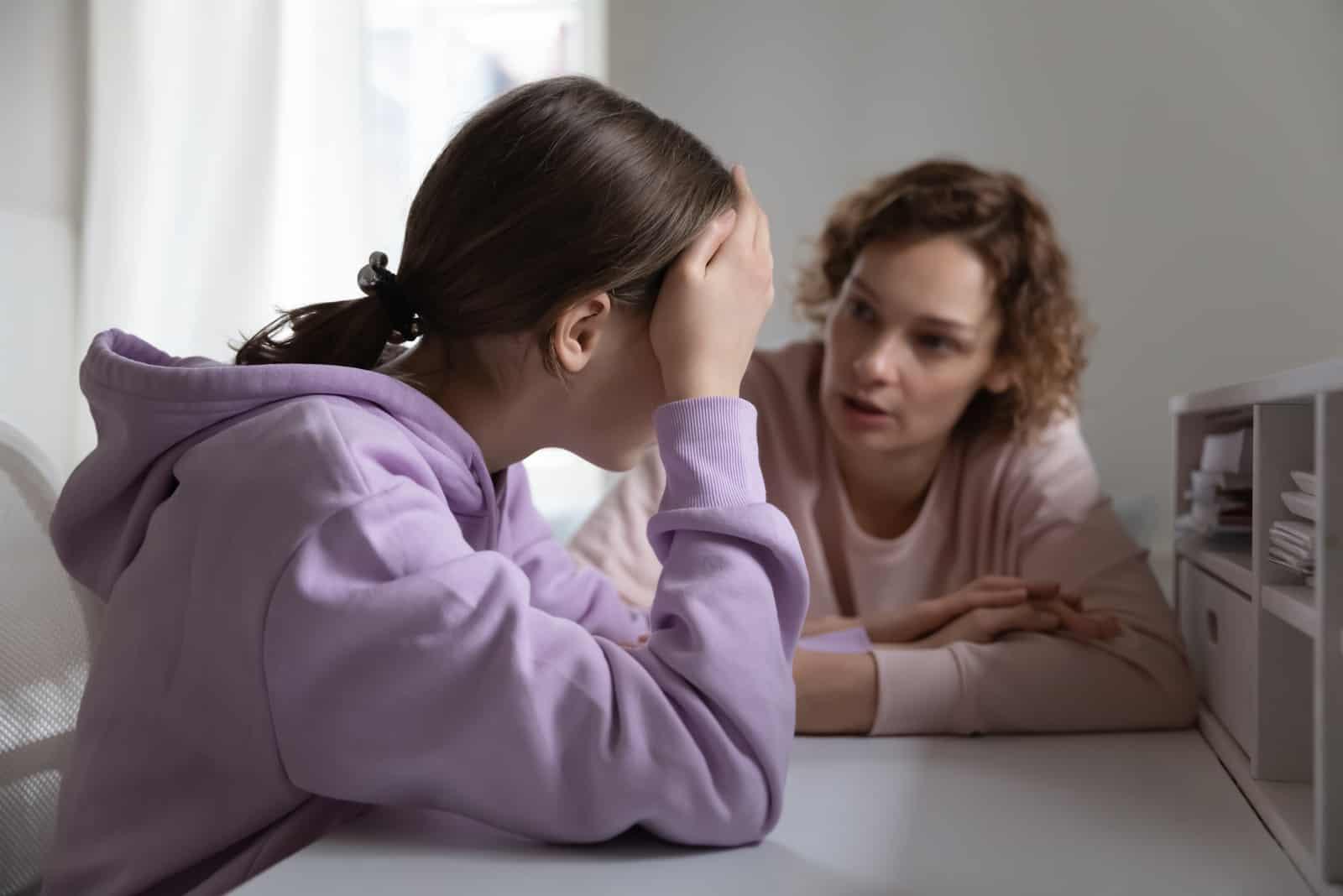 mère et fille s'assoient à table et parlent
