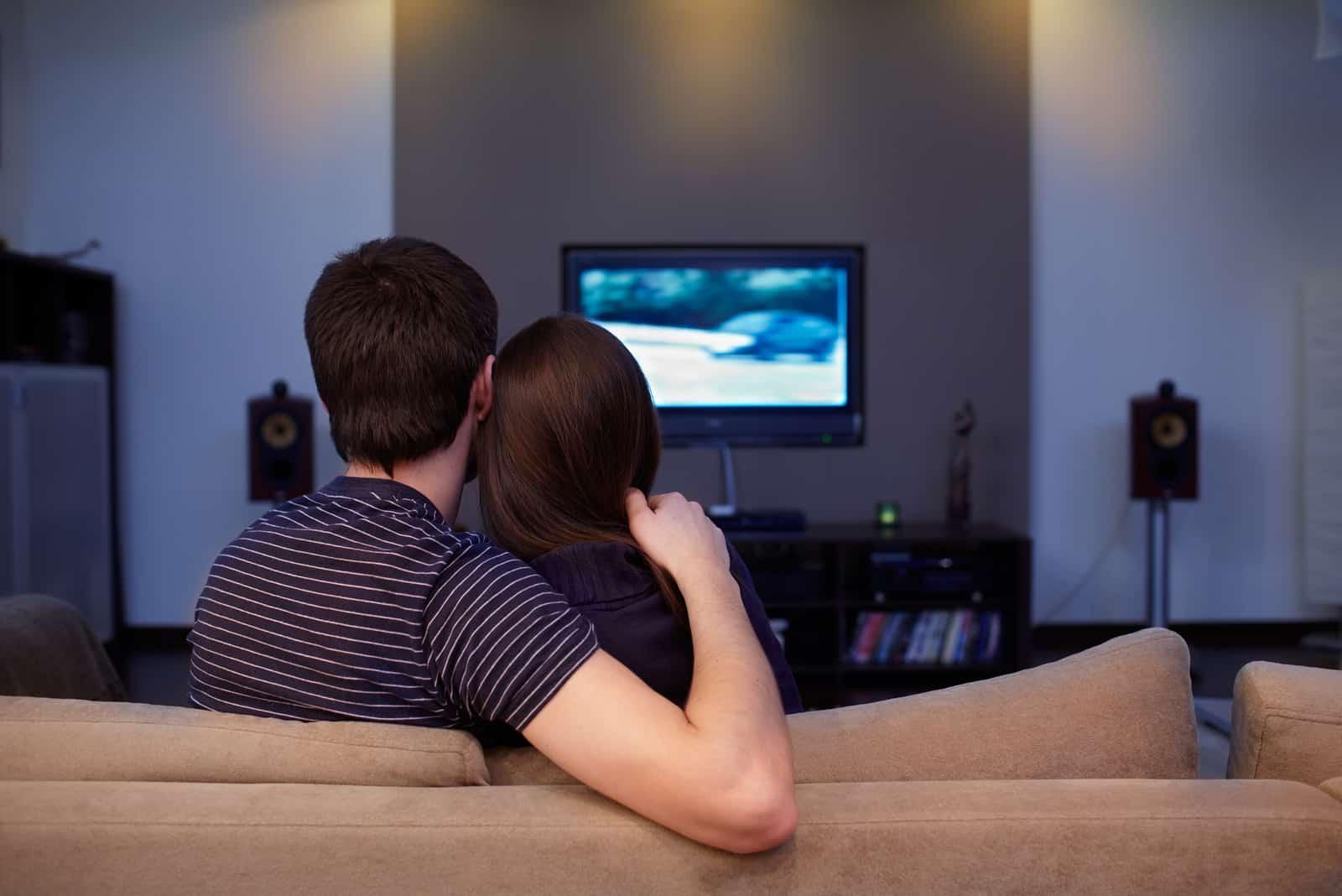 un couple amoureux embrassant assis et regardant la télévision