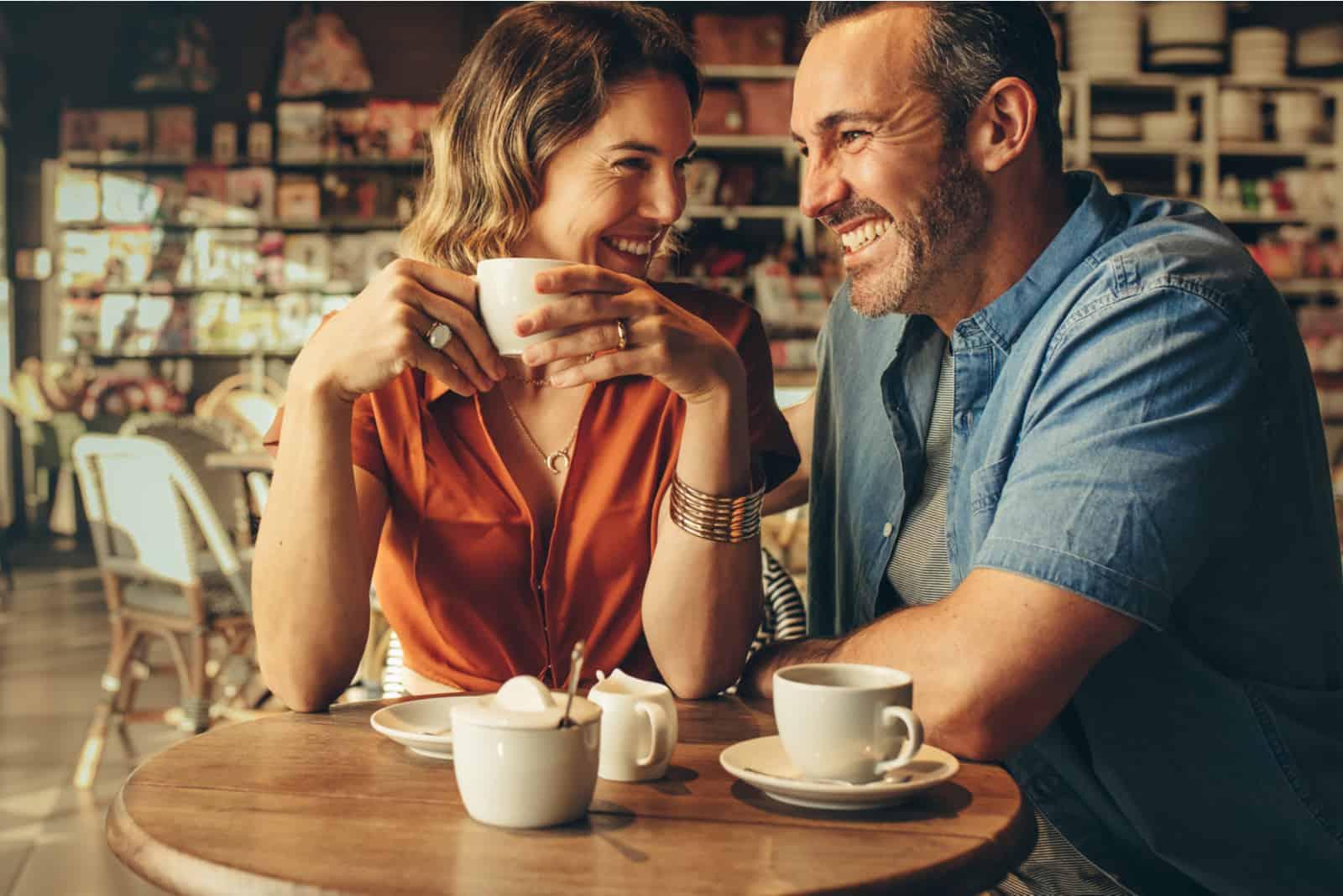 un couple d'amoureux souriant assis et buvant du café