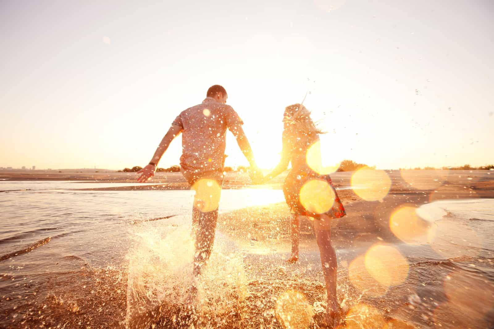 un couple heureux se tenant la main et courant sur la plage