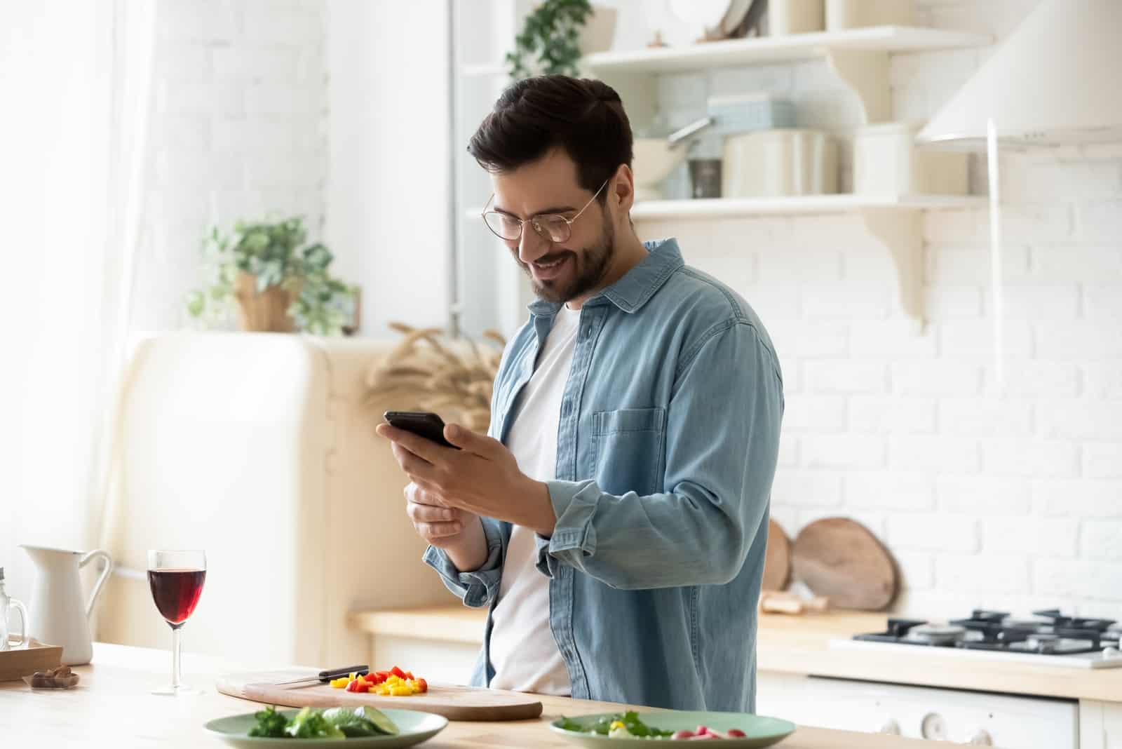 un homme avec des lunettes sur la tête est debout dans la cuisine et un bouton sur le téléphone
