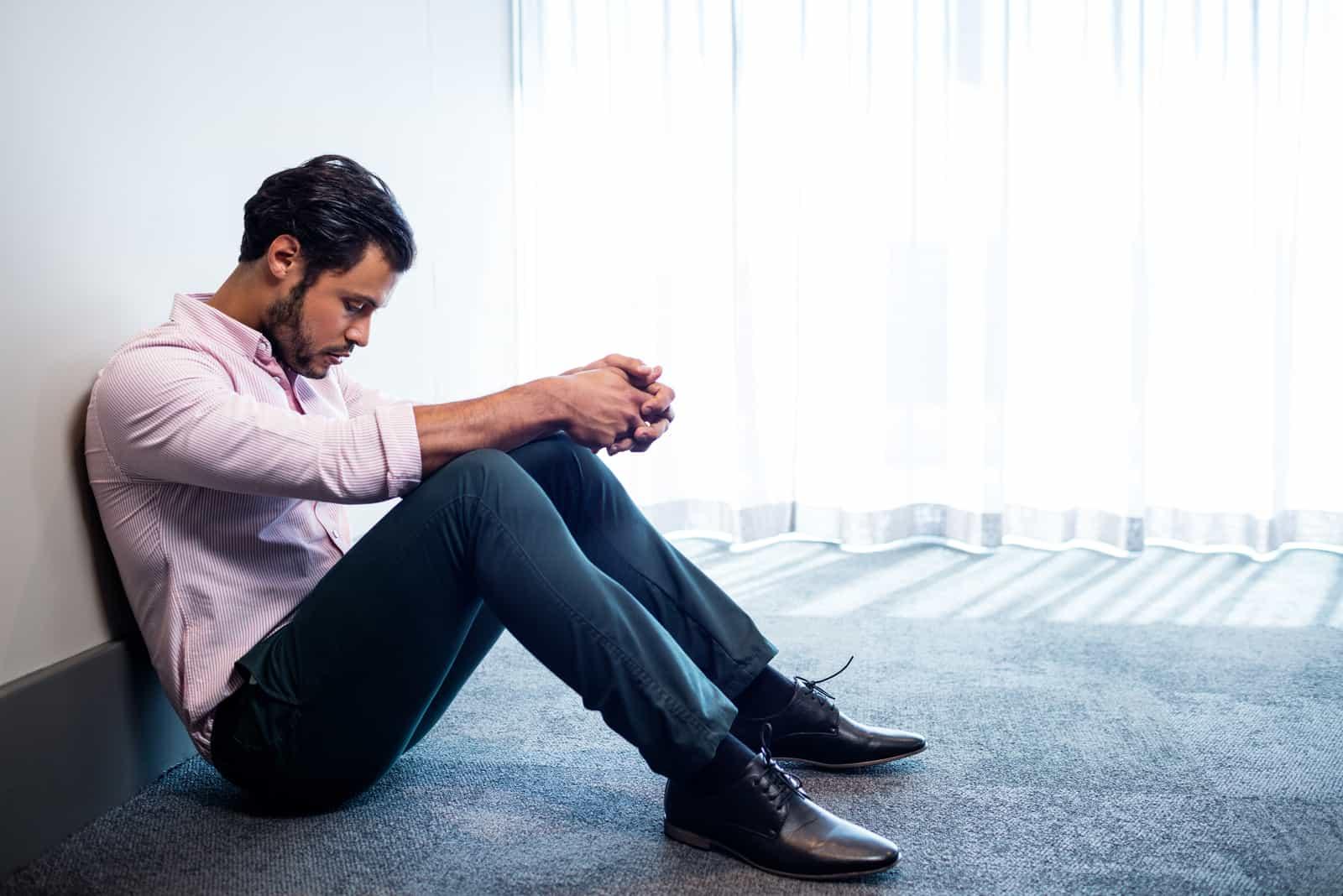 un homme déçu est assis par terre