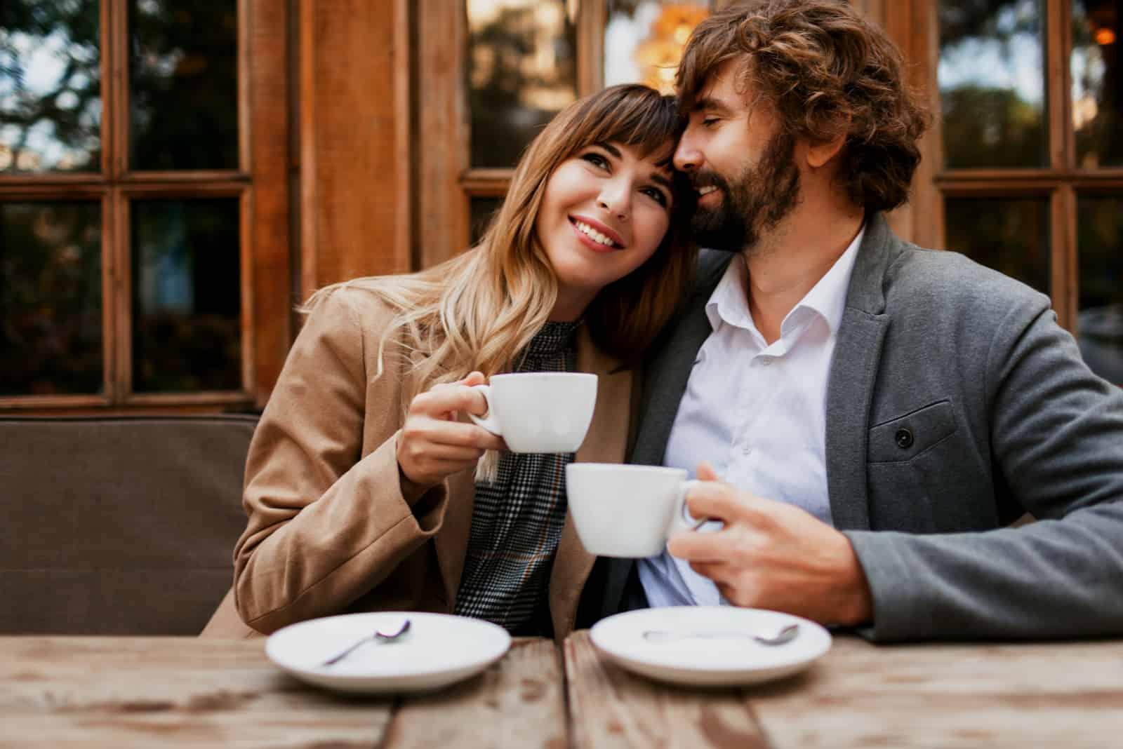 un homme embrasse une femme, il l'embrasse sur le front pendant qu'ils boivent du café