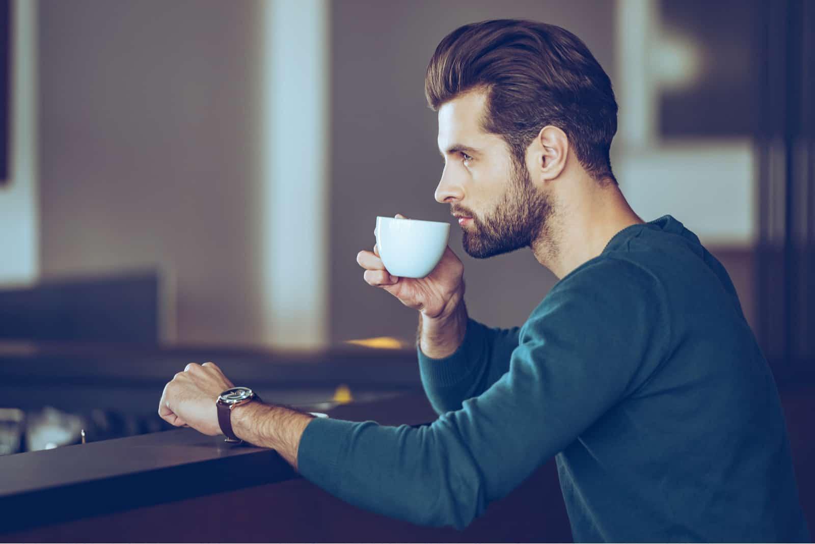 un homme est assis à une table et boit du café
