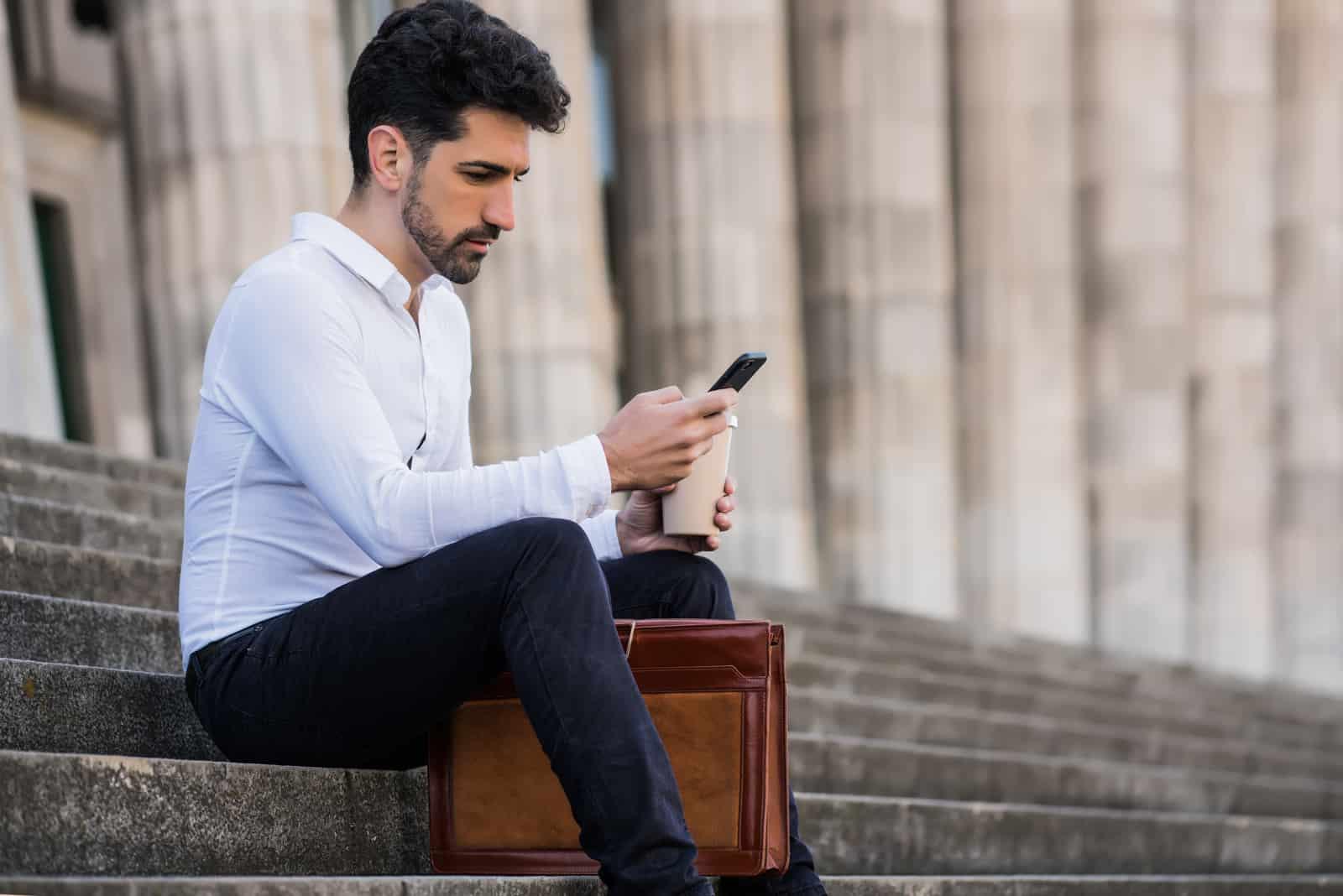 un homme est assis dans les escaliers et écrit au téléphone
