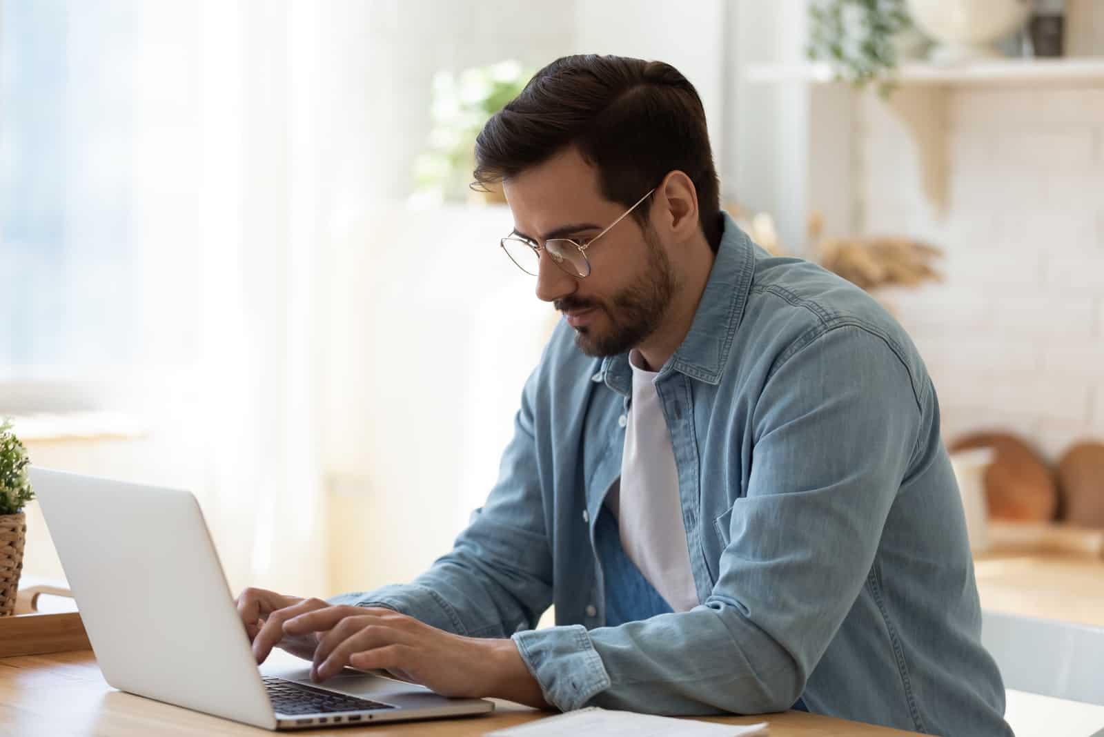 un homme est assis et un bouton sur un ordinateur portable