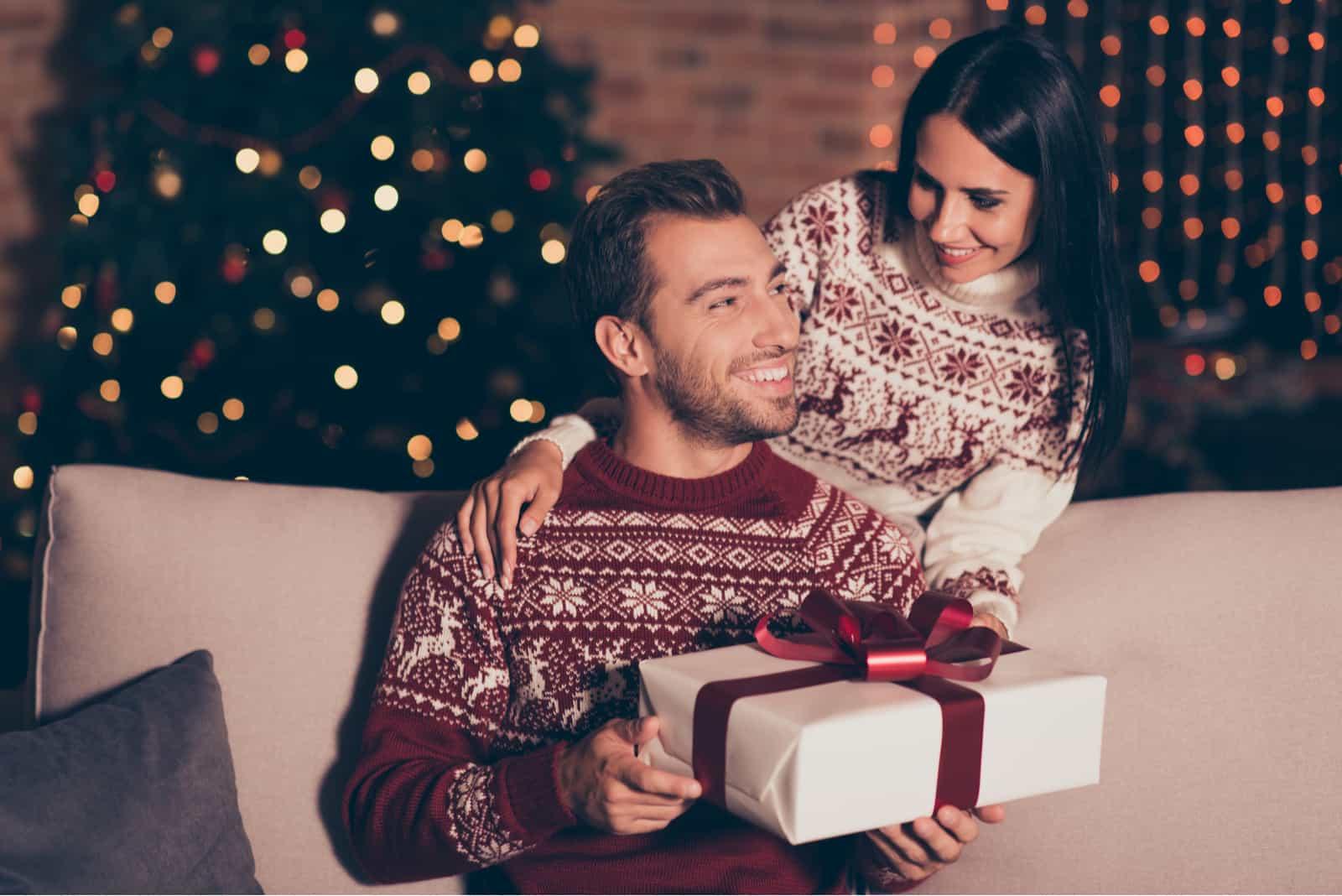 un homme et une femme avec un cadeau à la main