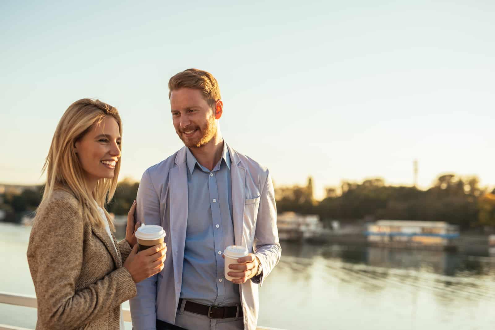 un homme et une femme debout tenant un café dans leurs mains et parlant