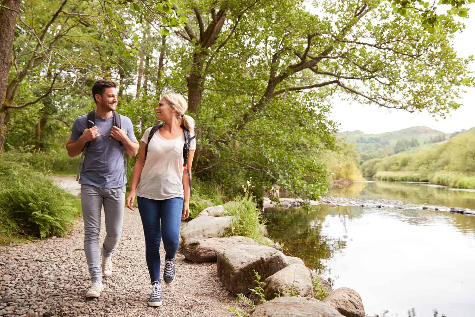un homme et une femme marchent le long de la rivière