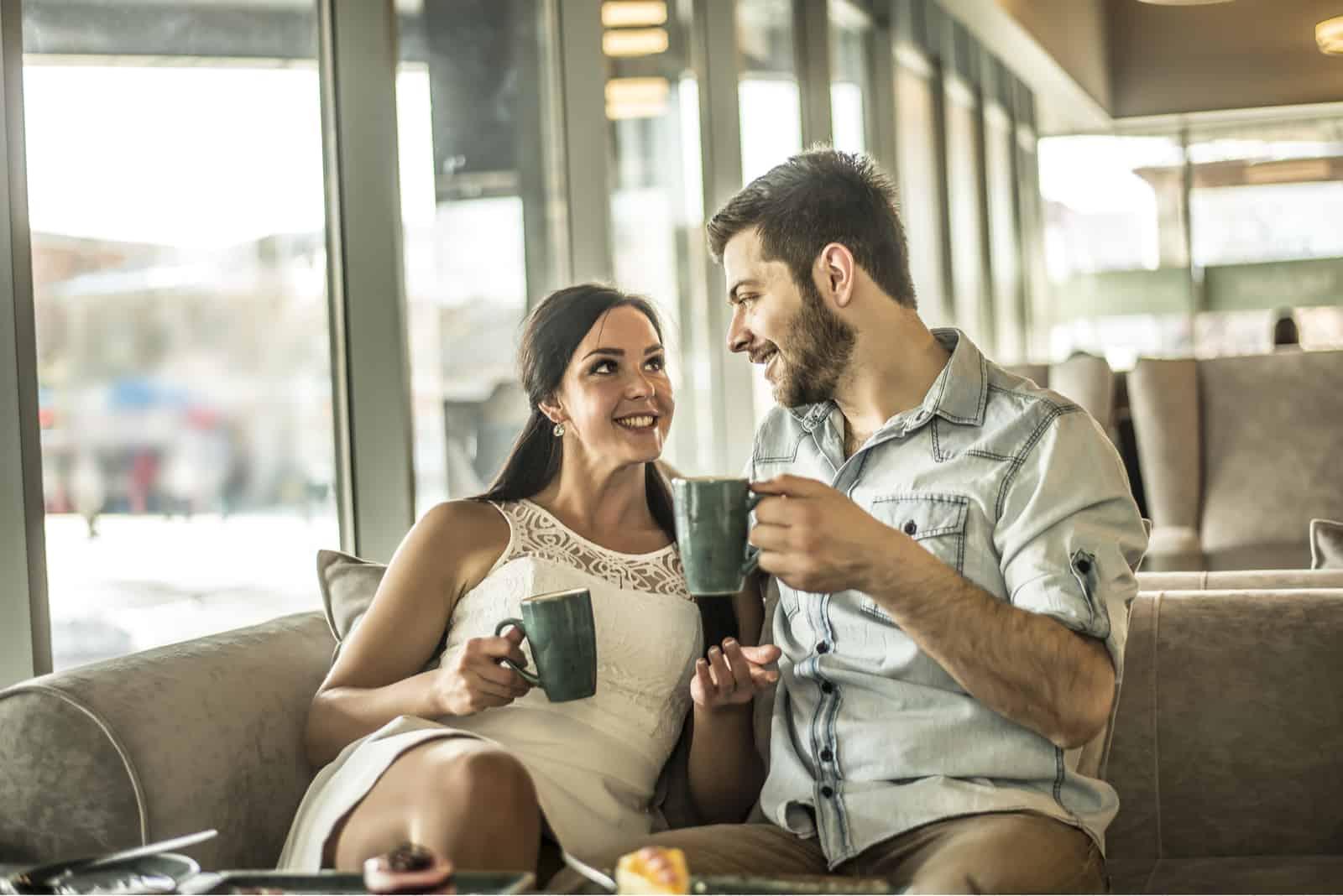 un homme et une femme s'assoient sur le canapé et boivent du café