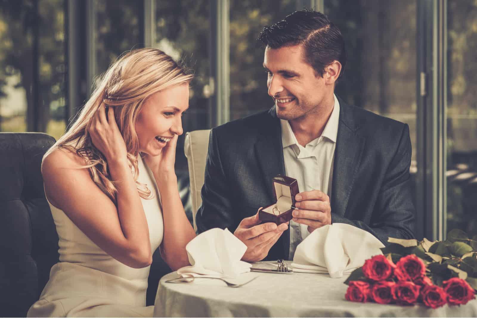 un homme et une femme sont assis à dîner il la supplie