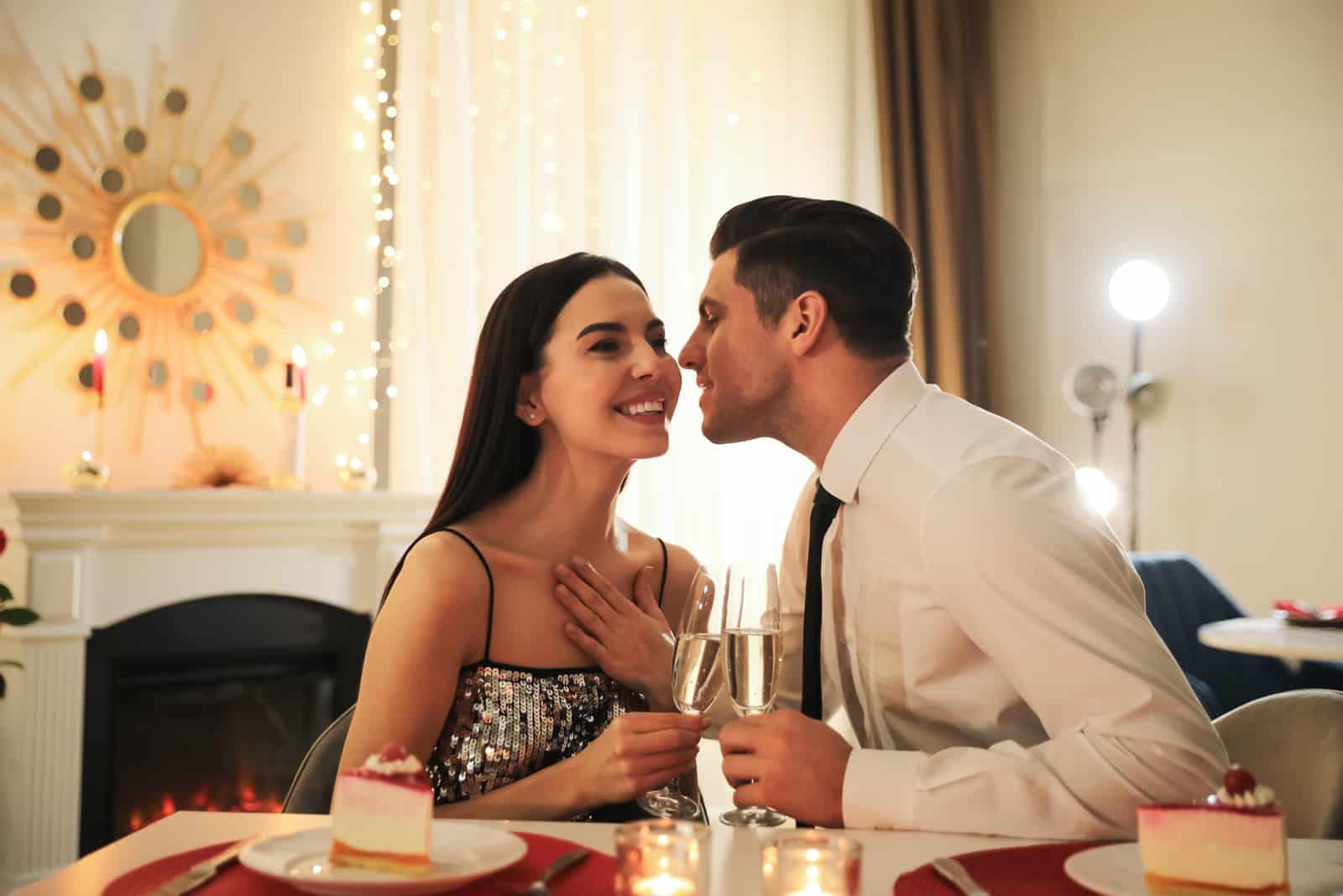 un homme et une femme sont assis à dîner, il veut l'embrasser sur la joue