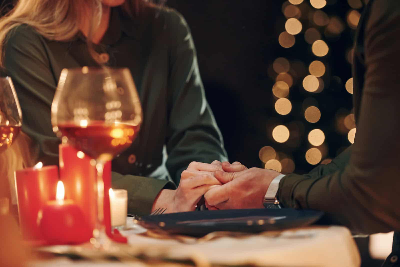 un homme et une femme sont assis à une table et se tiennent la main (2)