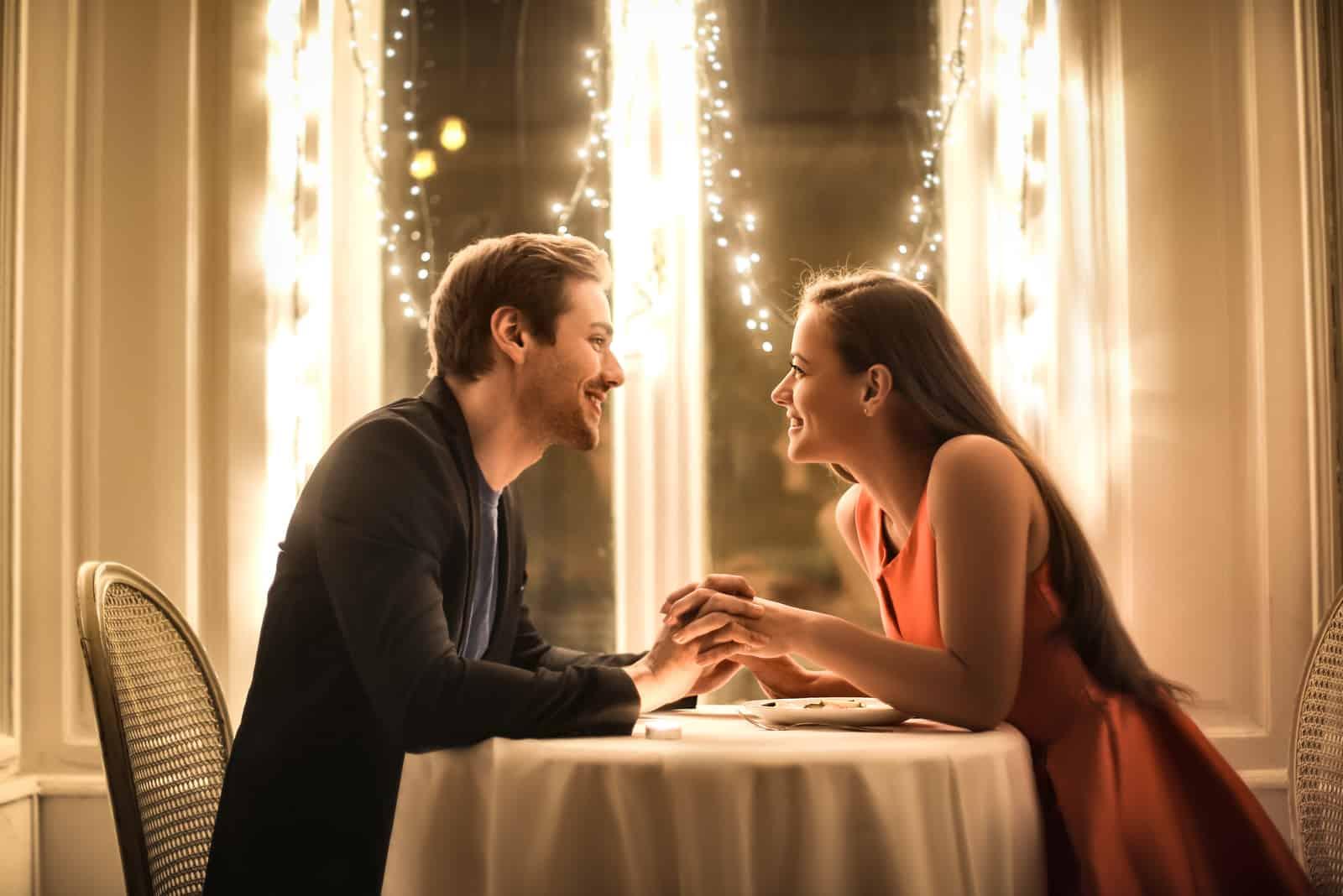 un homme et une femme sont assis à une table et se tiennent la main