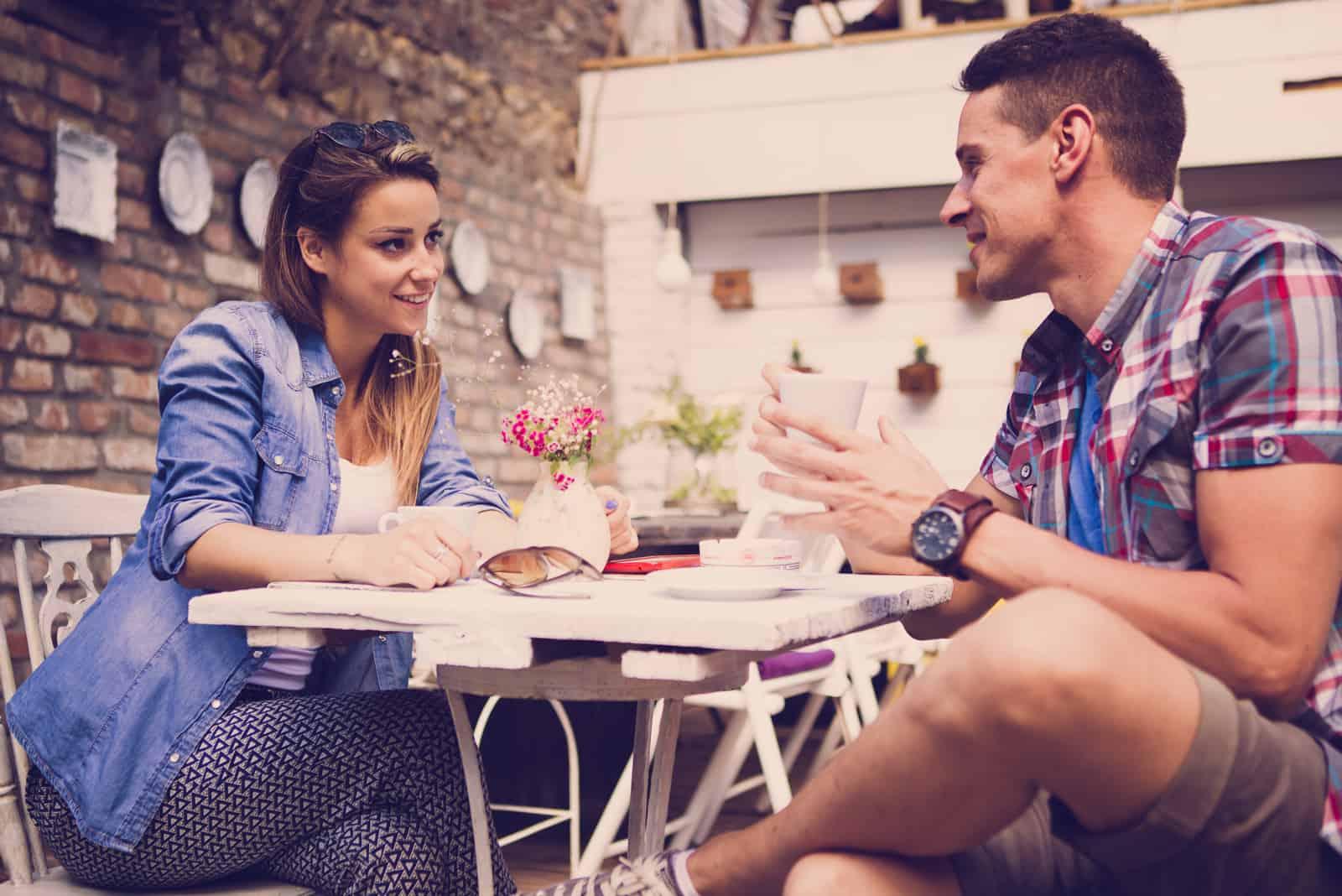 un homme et une femme sont assis dans un café et parlent autour d'un café