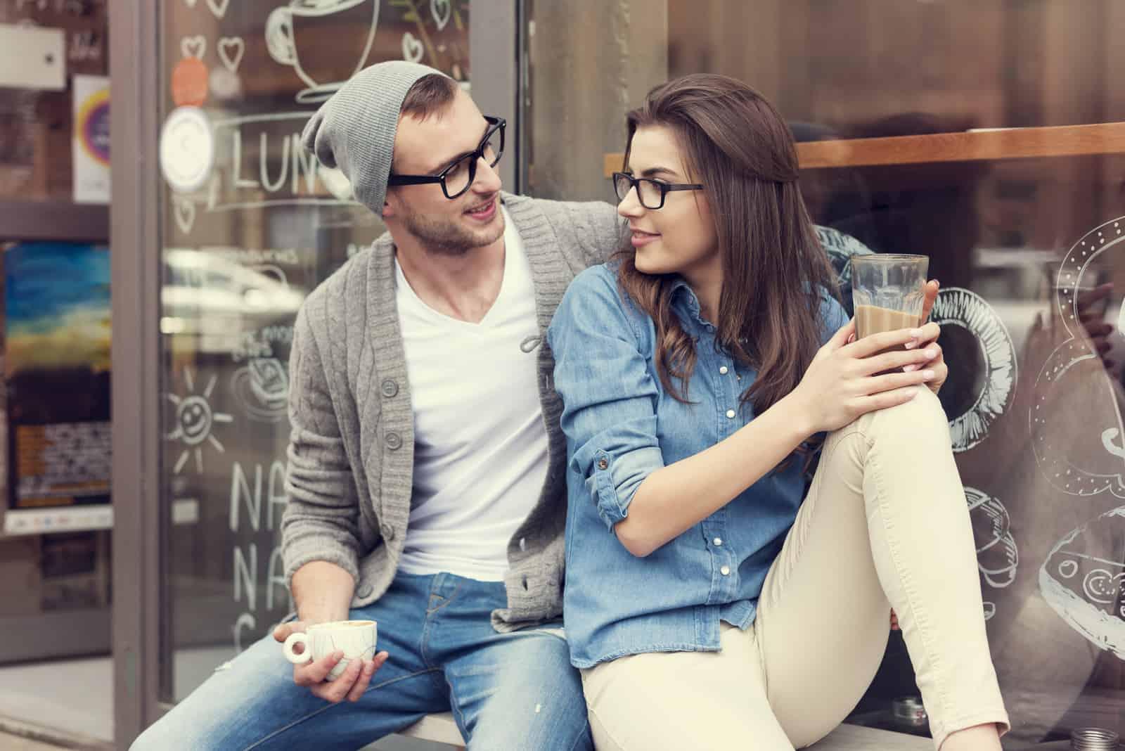 un homme et une femme sont assis dans une vitrine et boivent du café
