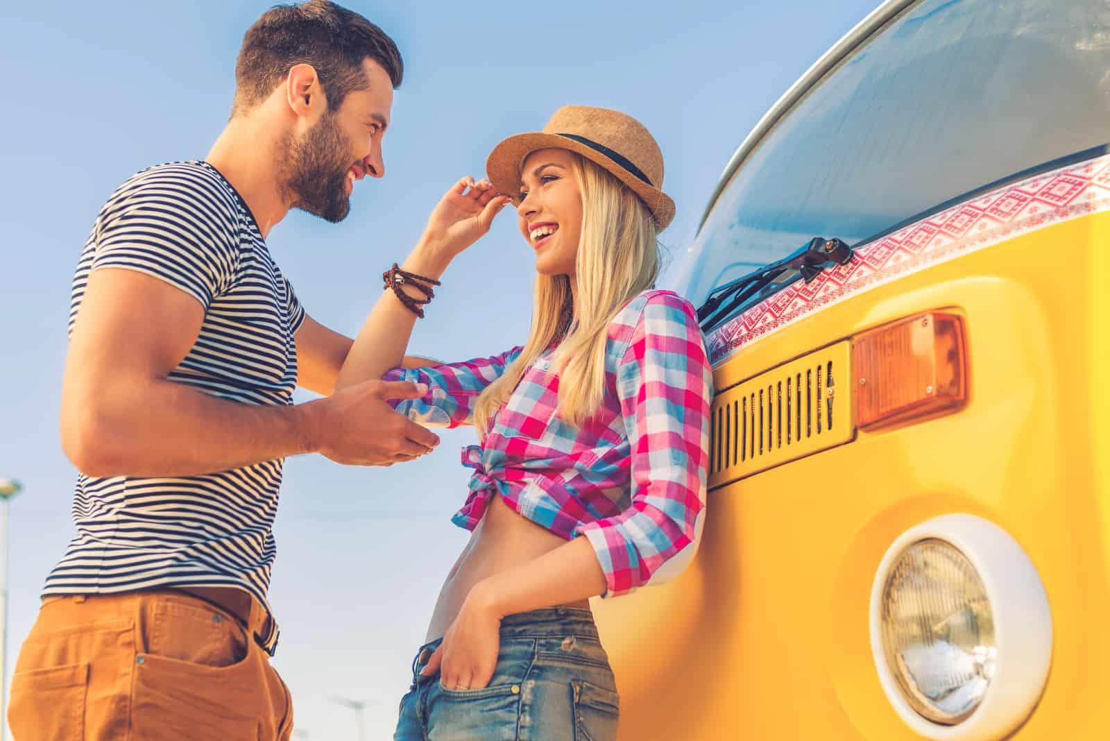 un homme et une femme souriants se tiennent appuyés contre le bus et parlent
