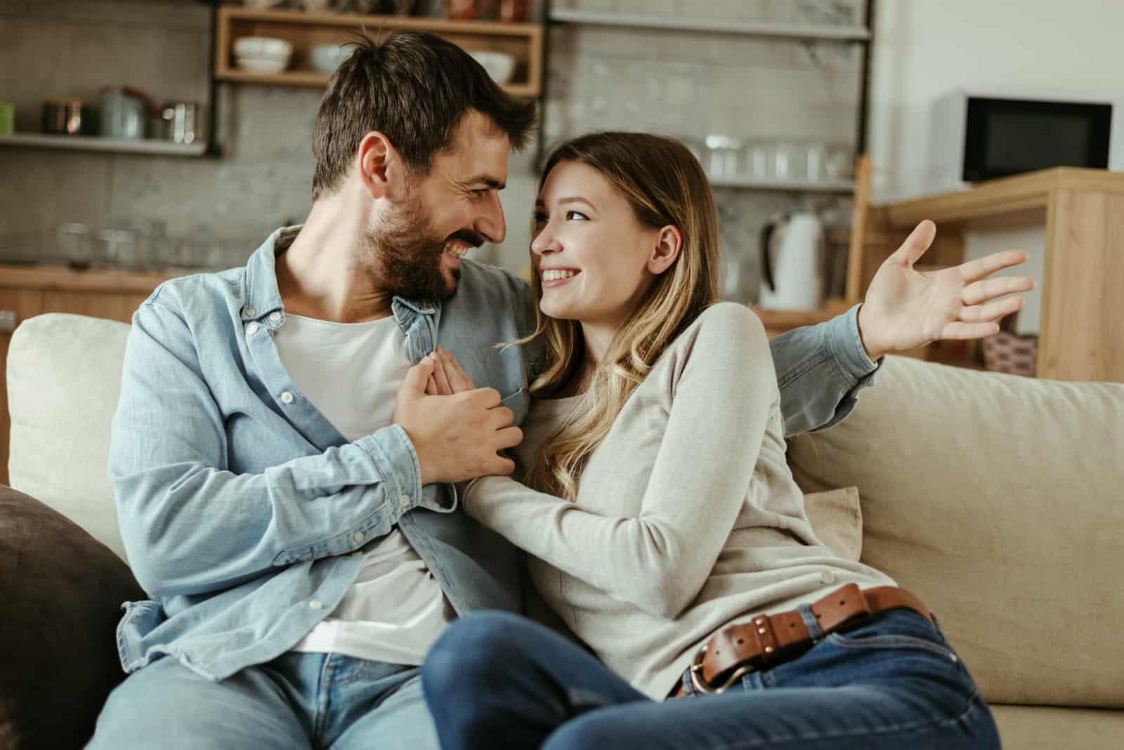 un homme et une femme souriants sont assis sur le canapé