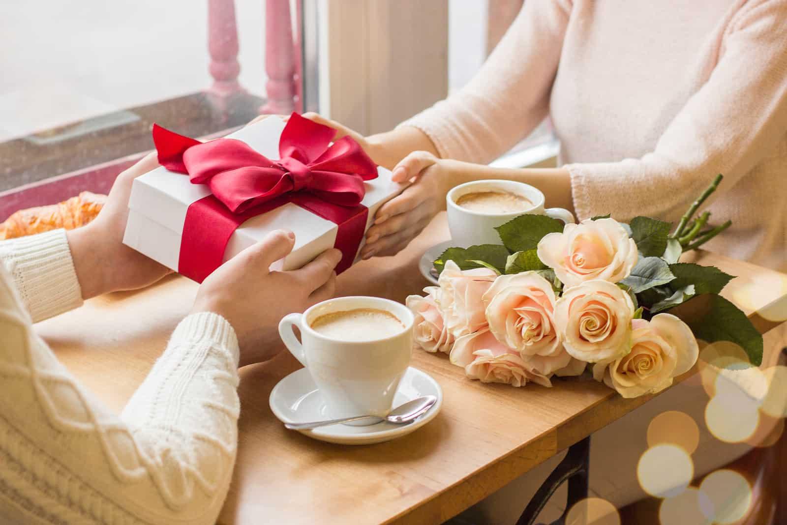un homme et une femme tiennent un cadeau sur la table