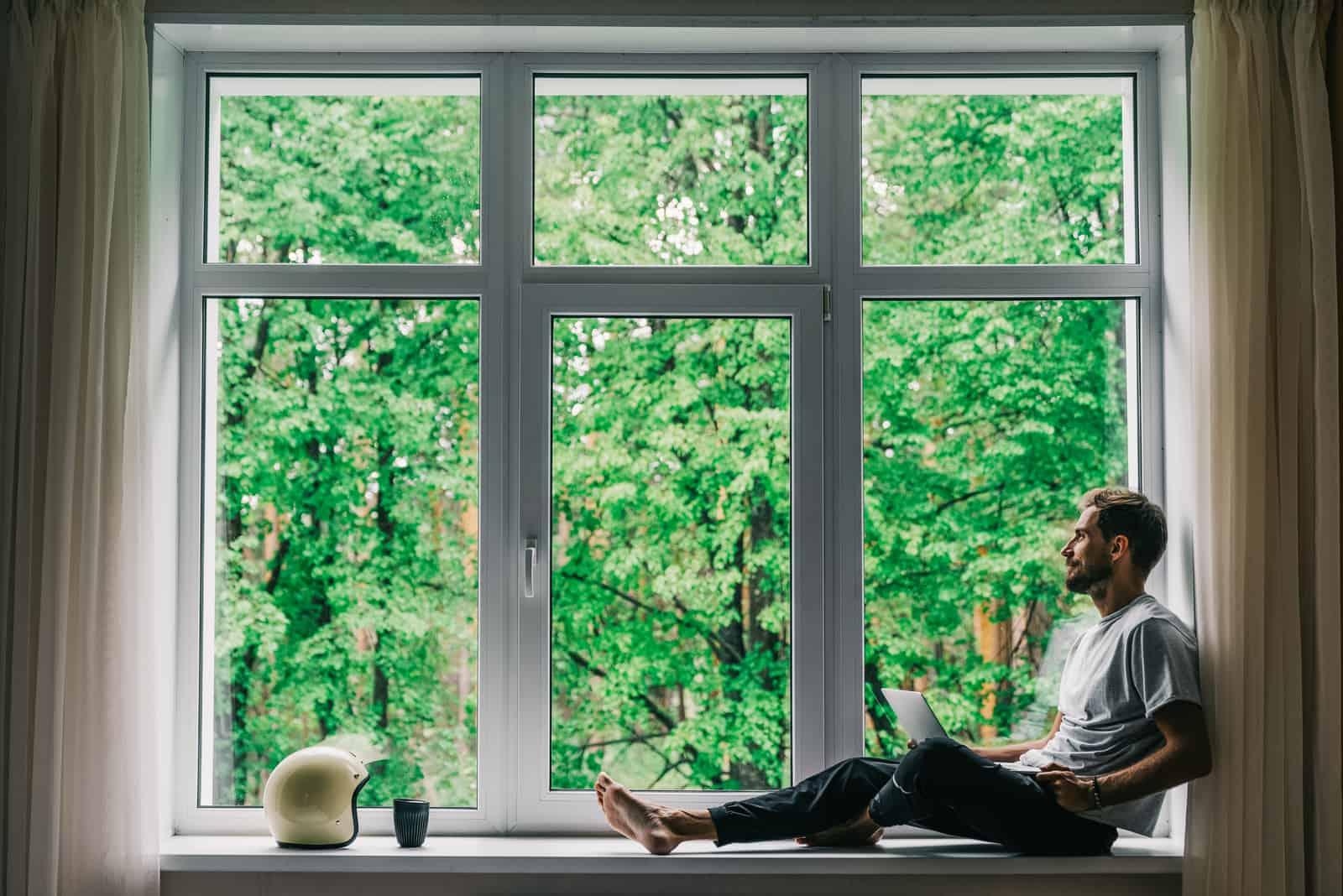 un homme imaginaire est assis à la fenêtre et regarde au loin