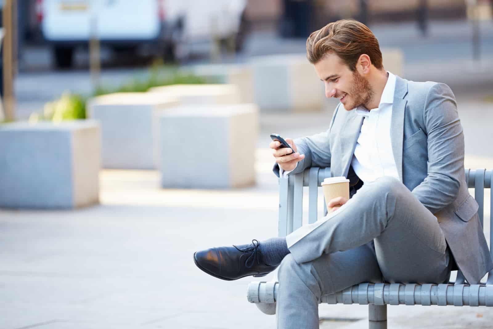 un homme souriant en costume est assis sur un banc de parc et les touches du téléphone